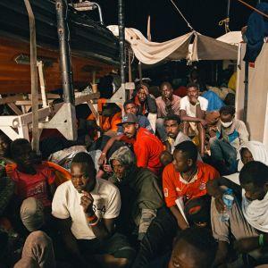 Joukko miehiä istuu laivan kannella.