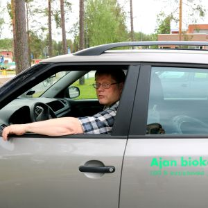 Mies istuu kuljettajan paikalla autossa, jonka kyljessä lukee sen kulkevan biokaasulla.