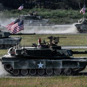 Tankki pellolla, jossa liehuu Yhdysvaltain lippuja.