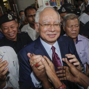 Najib Razak poliisin ja median ympäröimänä
