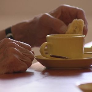 Kahvikuppi ja vanhuksen käsi pitämässä pullaa.