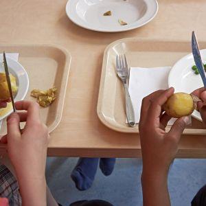 Koululaiset kuorivat keitettyjä perunoita lounaalla.