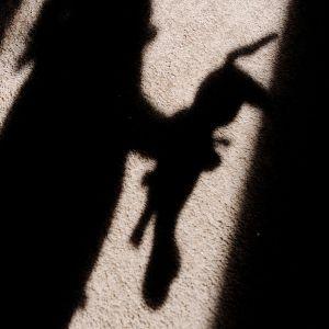 Varjokuvina näkyvät lapsi ja pehmolelu.