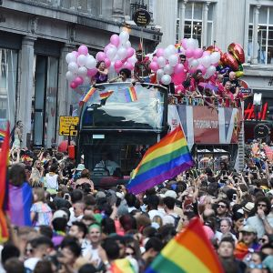 Katu on täynnä marssijoita, ja monet kantavat sateenkaaren värisiä lippuja. Kuvan keskiosassa keskellä ihmismerta on kaksikerroksinen bussi, jonka avoimessa yläosassa on ihmisiä valkoisten ja vaaleanpunaisten ilmapallojen kanssa.