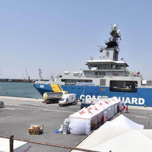Mereltä pelastteuja ja kuolleita tuodaan Catanian satamaan heinäkuussa 2017.