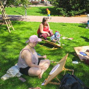 Ihmisiä maalaamassa puistossa.