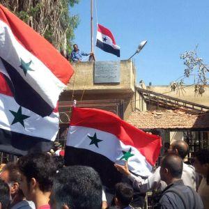 Syyrialaiset miehet heiluttavat Syyrian lippuja Tafaksen kaupungissa, Daraan maaseudulla.