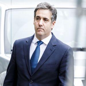 Cohen kävelee tummansinisessä puvussa, sininen kravatti kaulassaan, vakava ilme kasvoillaan.