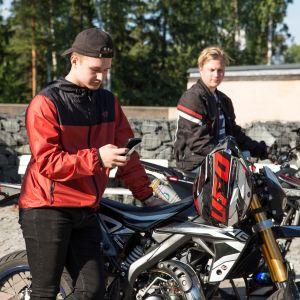 Kaksi teiniä poseeraa kevytmoottoripyöriensä vieressä.