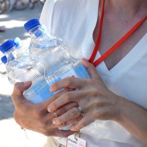 Nainen kantaa vesipulloja.