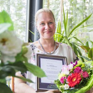 Nainen istuu Kajaaniin kylmäkaraisukeskuksessa sylissään diplomi ja kukkakimppu.