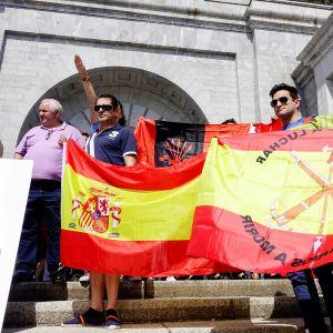 Miehiä iskulauseiden ja Espanjan lipun kanssa, taustalla henkilö tekee fasistitervehdystä.
