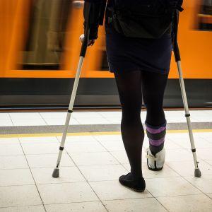 Kyynärsauvoihin nojaava nainen odottaa metroa.