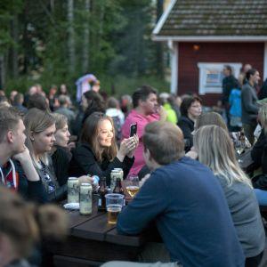 Paljon ihmisiä istumassa iltaa puisilla pitkillä penkeillä.
