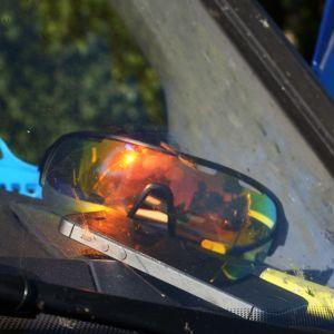 Kännykkä, sytkäri ja aurinkolasit autossa