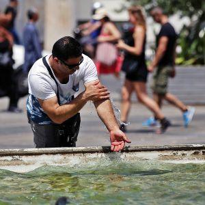 Mies viilentää itseään suihkulähteen vedellä.