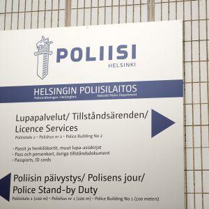Lupapalvelut -kyltti Helsingin poliisilaitoksen seinässä.