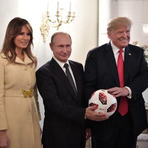 Melanialla on vaaleanruskea takki. Tummissa puvuissa olevat Trump ja Putin pitelevät jalkapalloa. Melania Trump ja Putin hymyilevät vienosti, Trump leveästi.