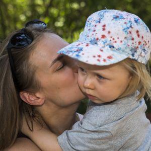 Äiti suutelee sylissän olevaa lasta poskelle