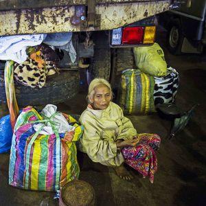 Nainen istuu suojassa tavaroineen.