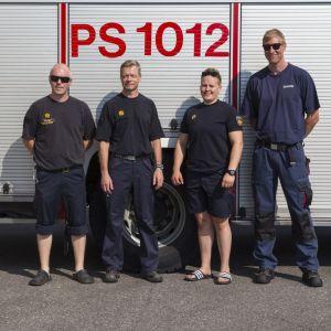 Ruotsiin metsäpalojen sammutukseen lähdössä oleva palomiesten ryhmän poseeraa paloauton edessä.