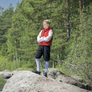 Jaakko Rikalainen kansallispuvussa koivu- ja järvimaisemassa.