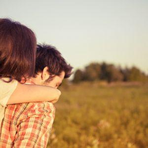 Mies ja nainen pellon reunalla kesäisessä maisemassa.