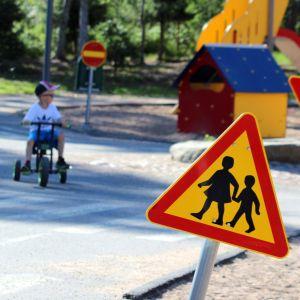 Pieniä lapsia leikkimässä lapsille rakennetulla liikennealueella.