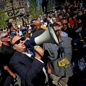 Alex Jones kovaääninen kädessään väkijoukon edessä