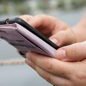 Nainen käyttää deitti-sovellusta älypuhelimella.