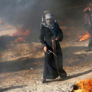 Palestiinalainen mielenosoittaja protestoi Israelin ja Gazan rajalla ritsa kädessään.