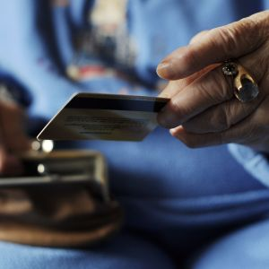 Vanhemman ihmisen käsi pitelee pankkikorttia.
