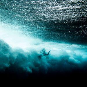 Vedenalainen kuva surffarista Tahitilla.