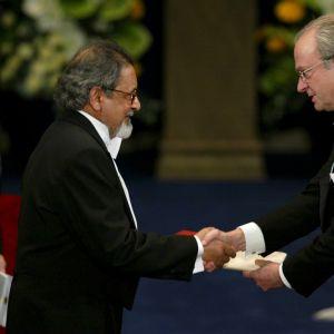 Kirjailija V.S. Naipaul kättelee Ruotsin kuningas Kaarle XVI Kustaata.