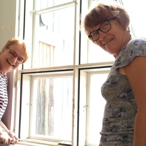 Ikkunoita rappaamassa kaksi naista.