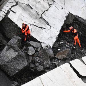 Pelastusmiehiä romahtaneen sillan jäännöksissä.