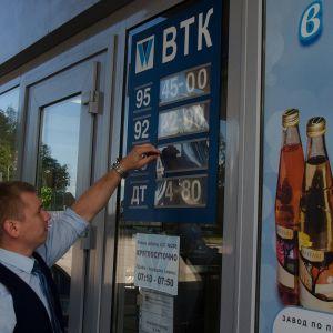 Myyjä laittaa bensanhintatietoja  näkyville.
