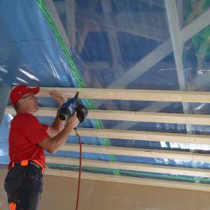 Mies kiinnittää lautoja rakenteilla olevan omakotitalon kattoon.