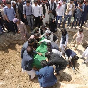 Ihmiset osallistuivat hautajaisiin päivä itsemurhahyökkäyksen jälkeen.
