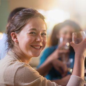 Nainen kohottaa lasia kameralle.