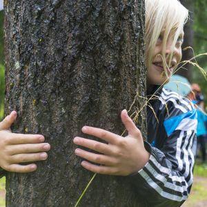 Poika halaa puuta ja hymyilee.