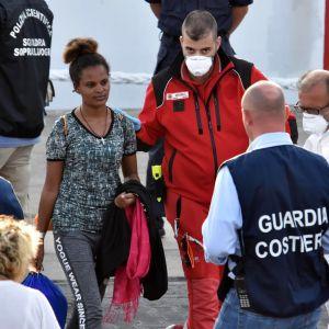 Eritrealainen nuori nainen saatettiin ulos laivasta Catanian satamassa.