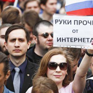 Kuva väkijoukosta Moskovassa. Mustiin laseihin sonnustautunut nainen pitelee lappua, johon on kirjoitettu venäjäksi: Kädet irti internetistä.