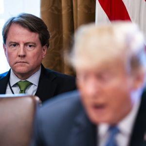 Don McGhan istuu taka-alalla ja kuuntelee vakavana kuvassa etualalla puhuvaa Donald Trumpia. McGahnilla on tummansininen puvuntakki, kauluspaita ja vihreä kravatti.