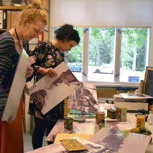 Kaksi naista tutkii valokuvatauluja museon toimistossa