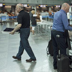 Matkustajia turvatarkastuksessa.