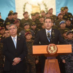 Kuvassa presidentti puhuu puhujanpöntössä, taustalla armeijan barettipäisiä sotilaita.