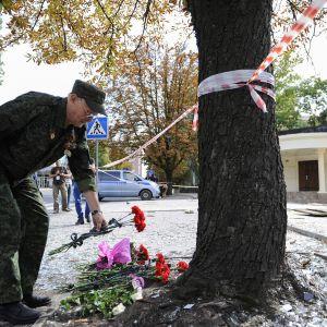 Mies asettaa kukkia ravintolan luona jossa Aleksander  Zahartšenko sai surmansa.