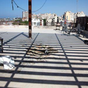 Katossa näkyvissä kuoppa, jonka raketti-isku on aiheuttanut. taustalla siintää muita Tripolin rakennuksia ja sininen taivas ja meri.