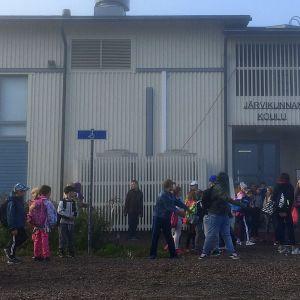 Lapset odottavat suljetun koulun pihalla bussikyytiä Tönnön ja Myllylän kouluihin.